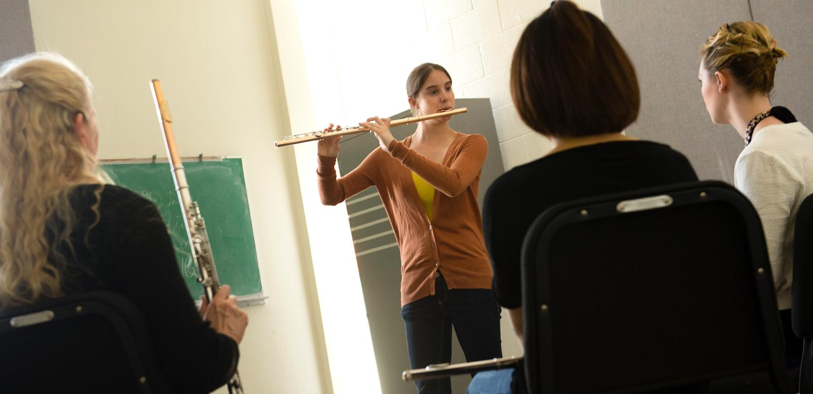 group of students and professor observing flute player