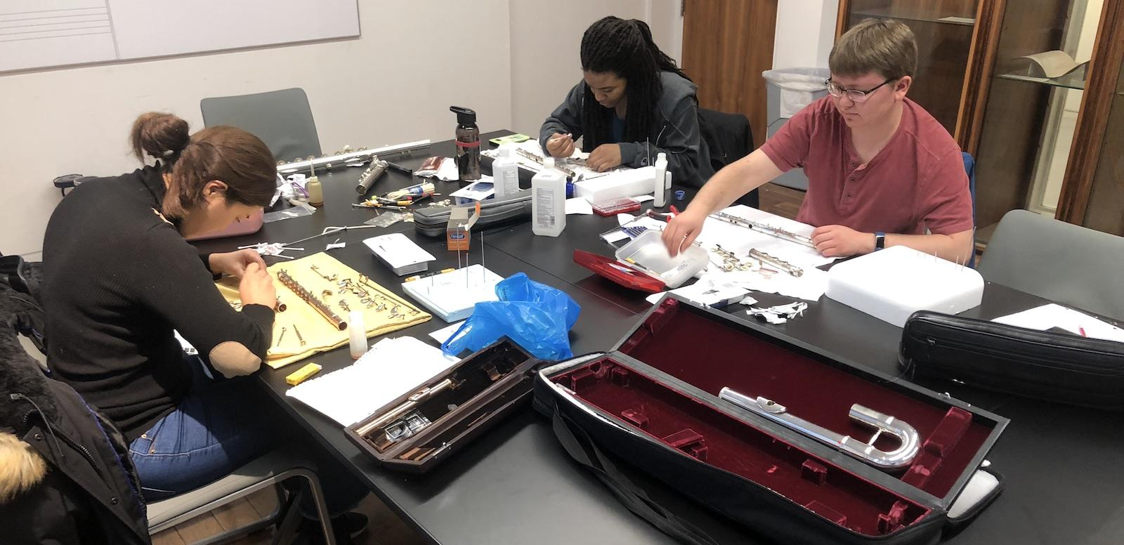 three students sitting at a table taking apart flutes and cleaning them