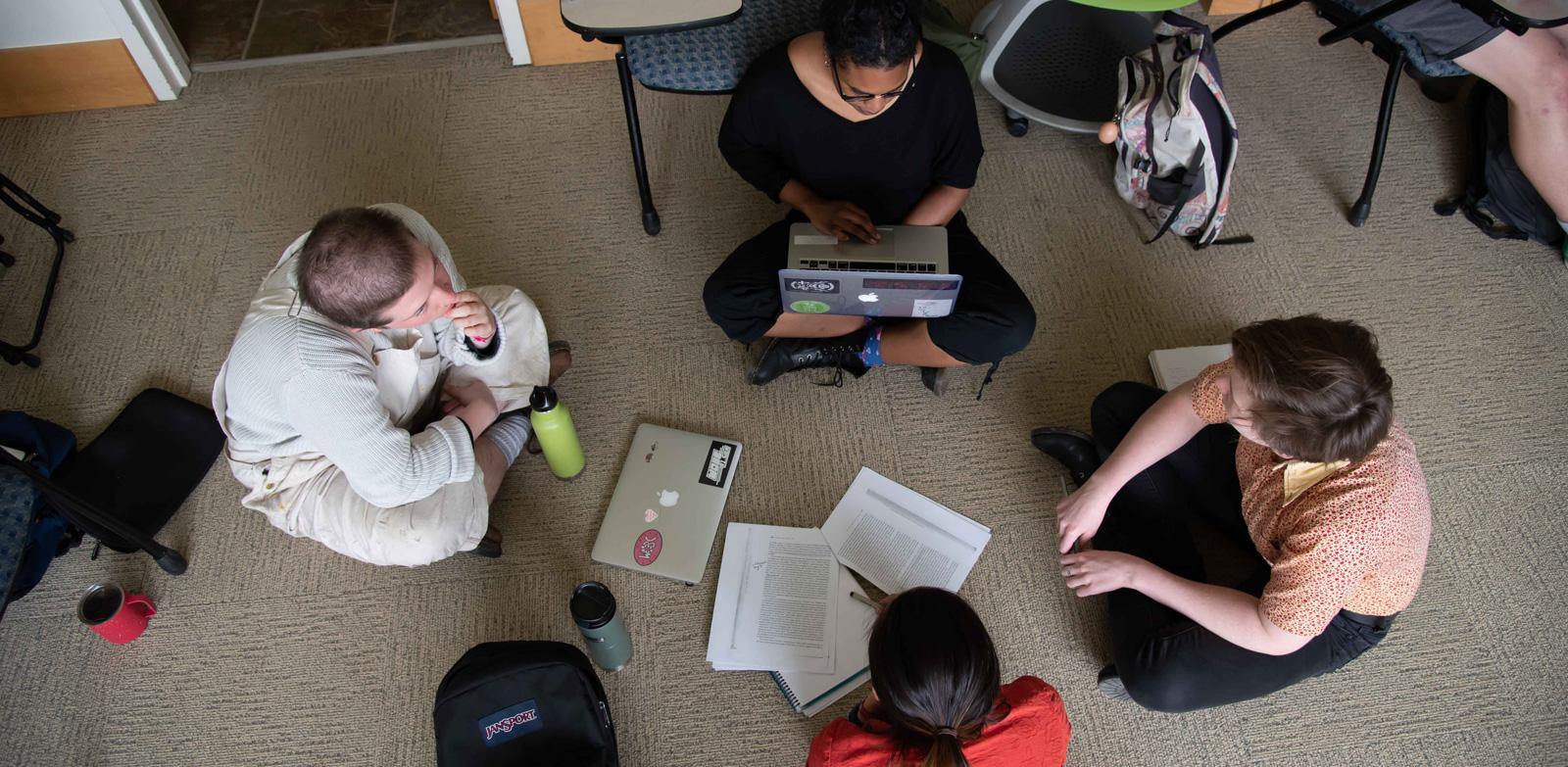 Four students sit together on the floor, working on a group project. Viewed looking down from above.