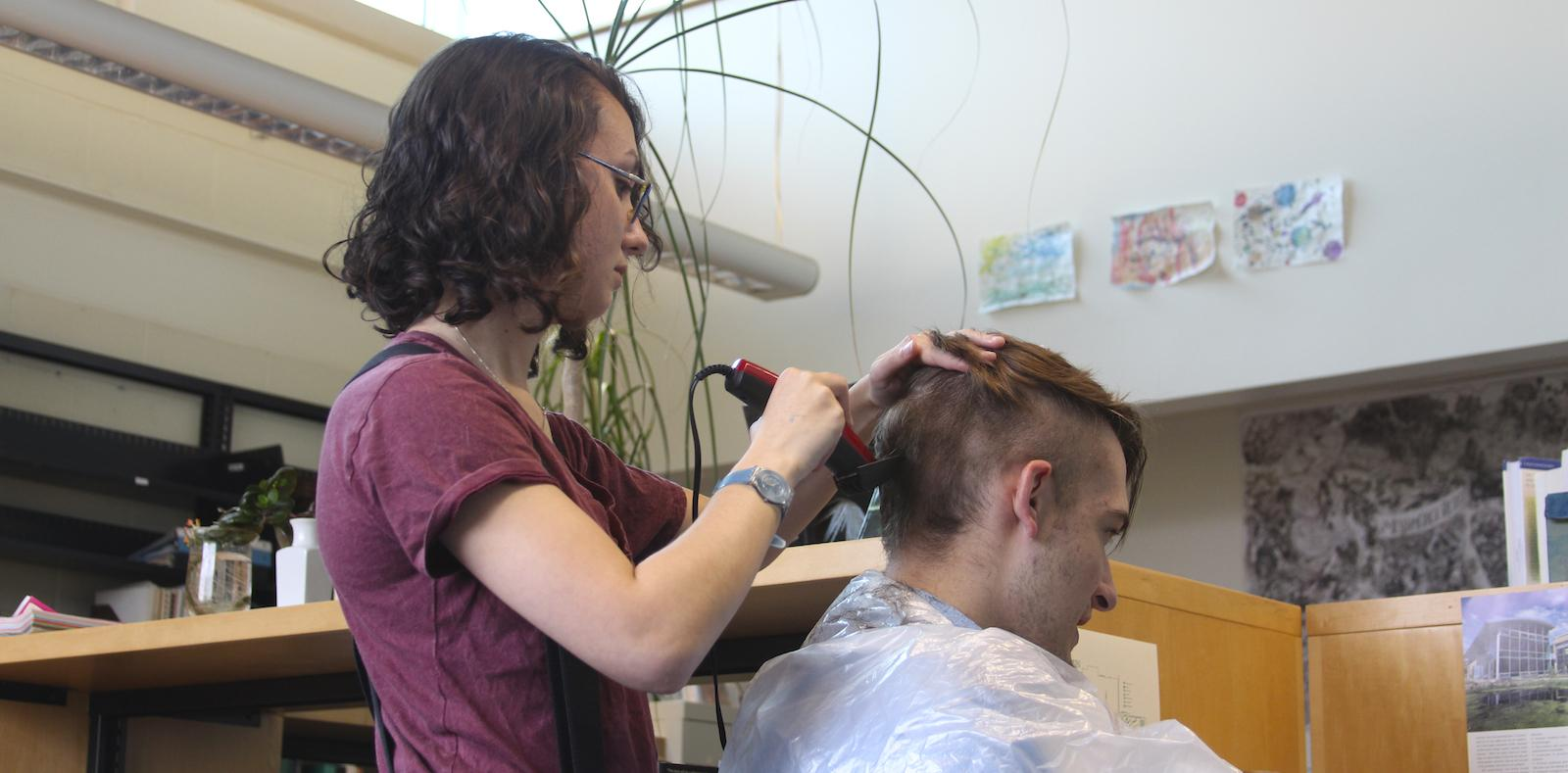 One student cuts another's hair with electric trimmers