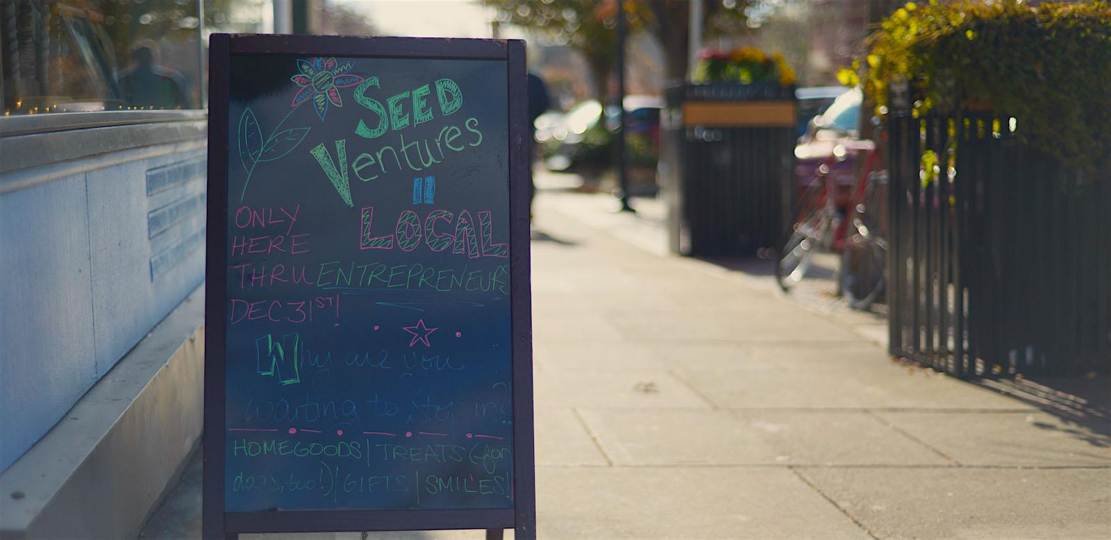A hand-drawn sign by a storefront reads Seed Ventures - Local Entrepreneurs. Only open thru Dec 31st! Why are you waiting to stop in? Home goods, treats (for dogs too), gifts, smiles!