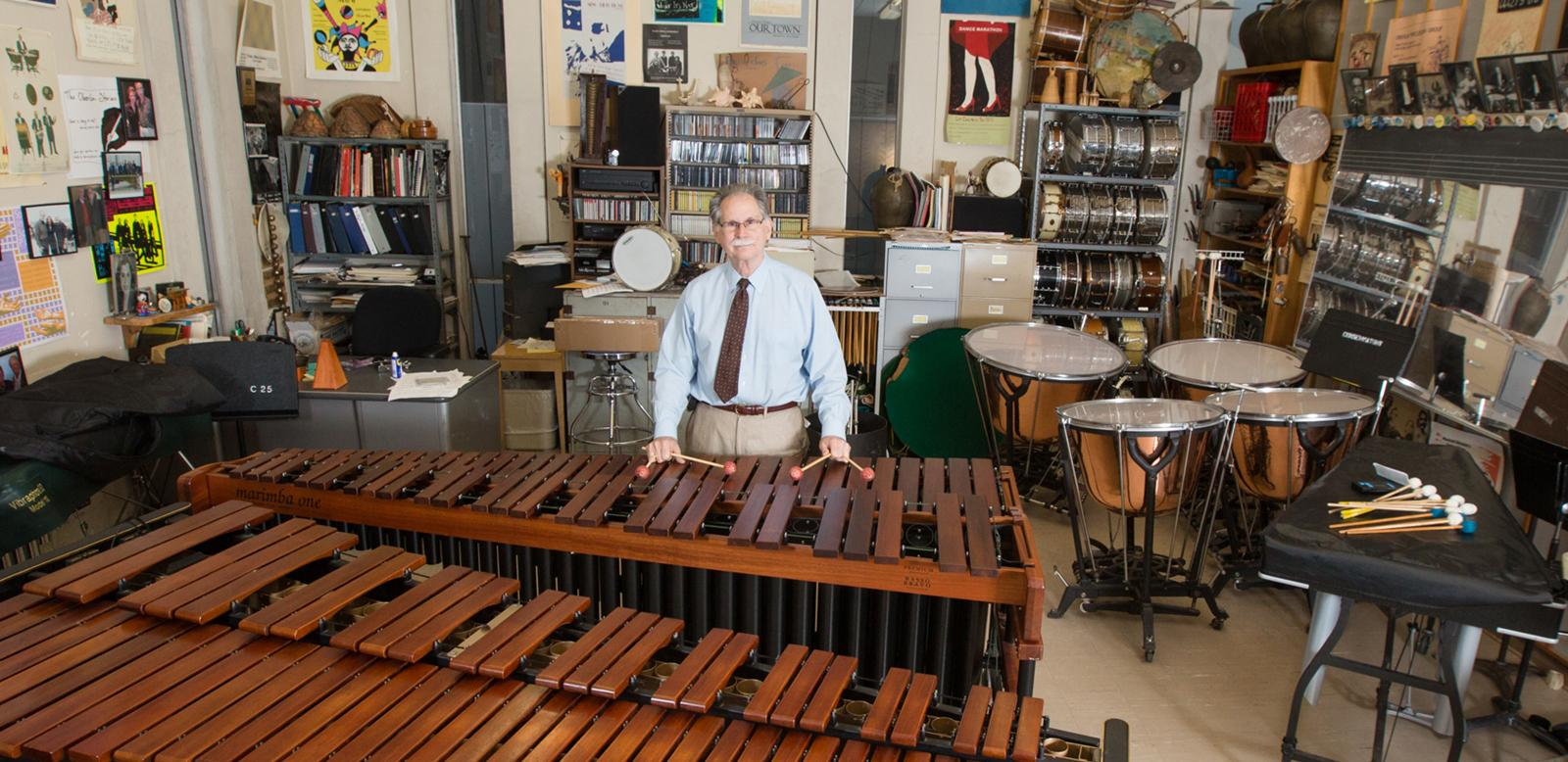 Professor in studio surrounded by percussion instruments