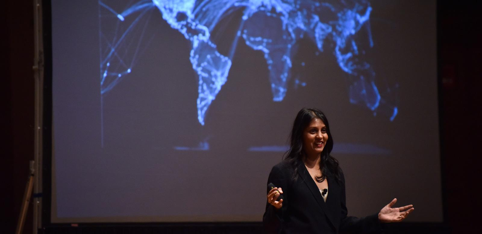 A woman gives a presentation in front of a large screen showing a map of the world's continents.