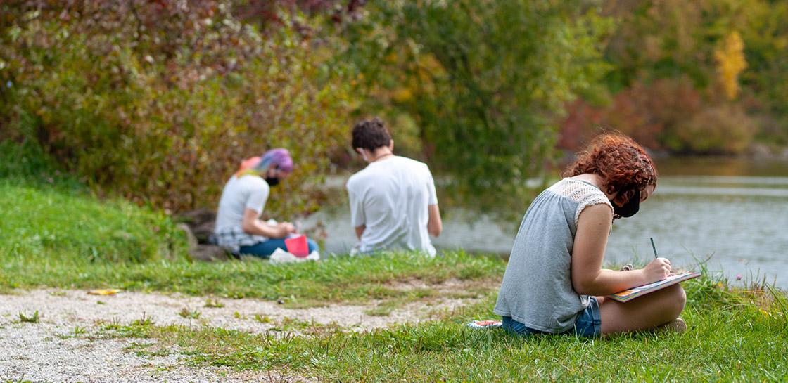 Students sketch while sitting in the grass by a scenic pond.