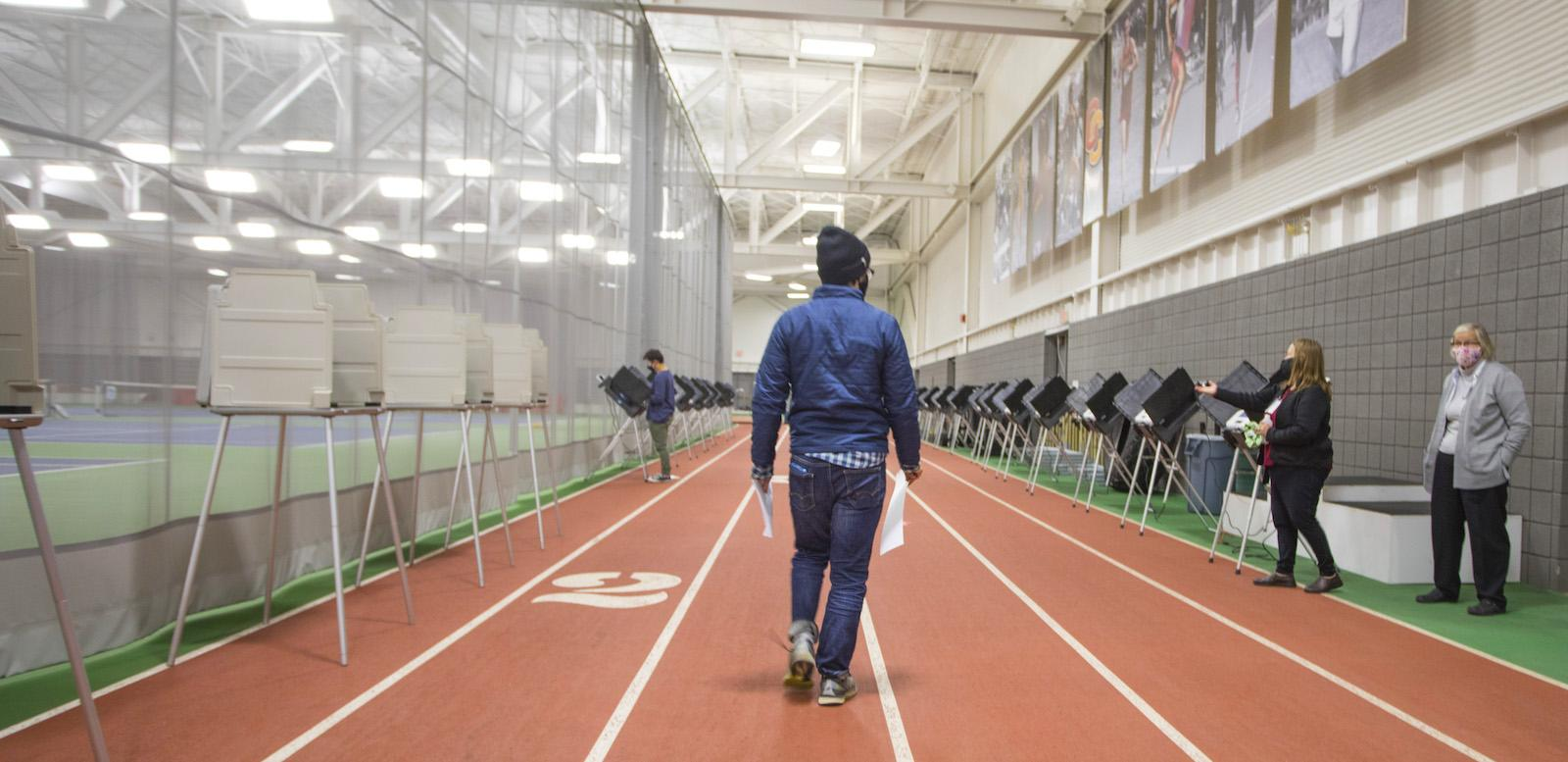 person walking on a indoor track toward a voting booth.
