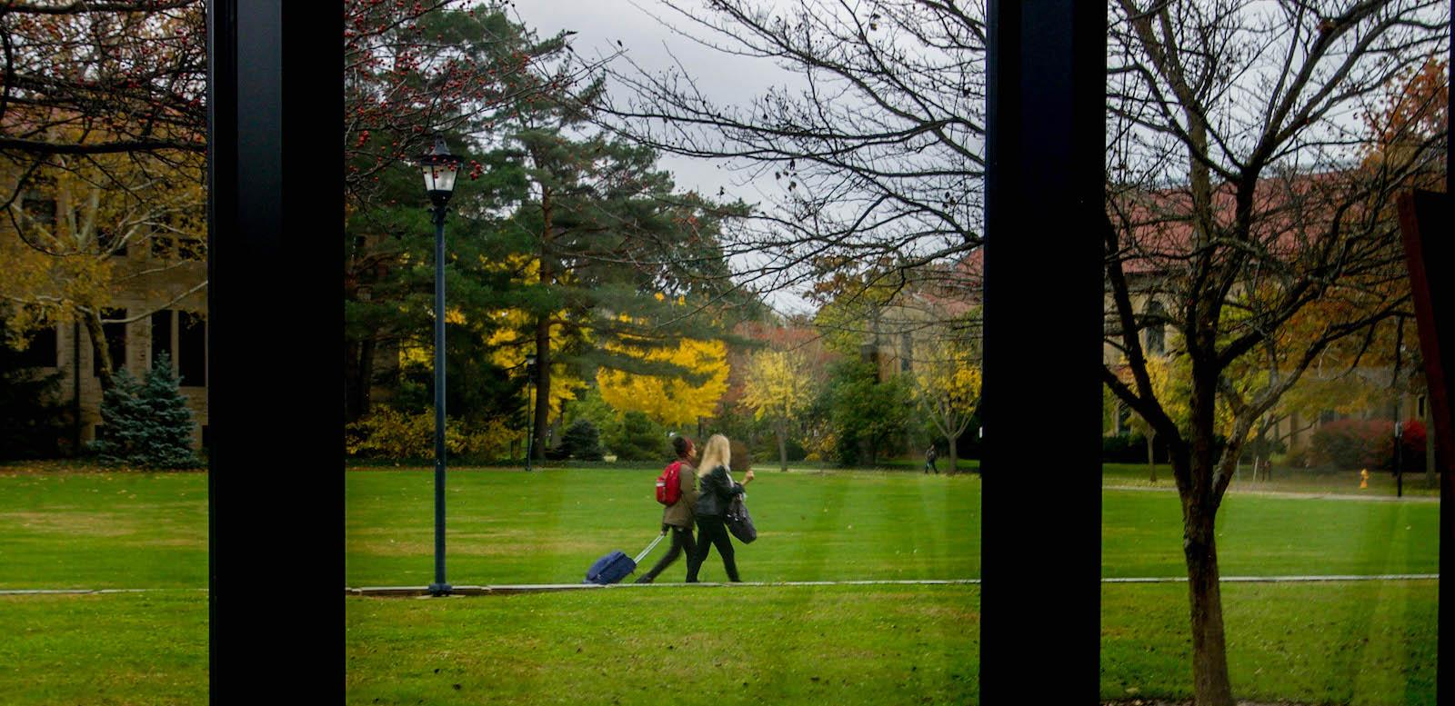 two people walking across campus with suitcase.