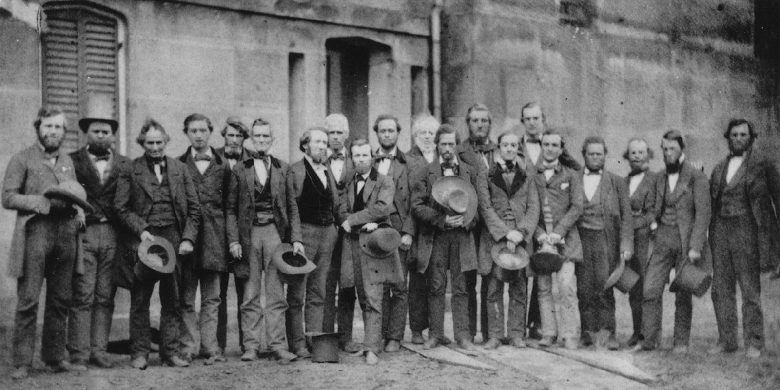 Historical photo of 20 men standing together, holding their hats.