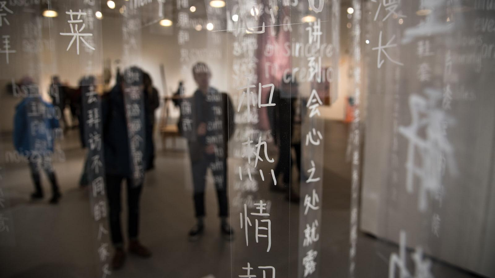 Students behind clear, long strips with Chinese writing in white letters.