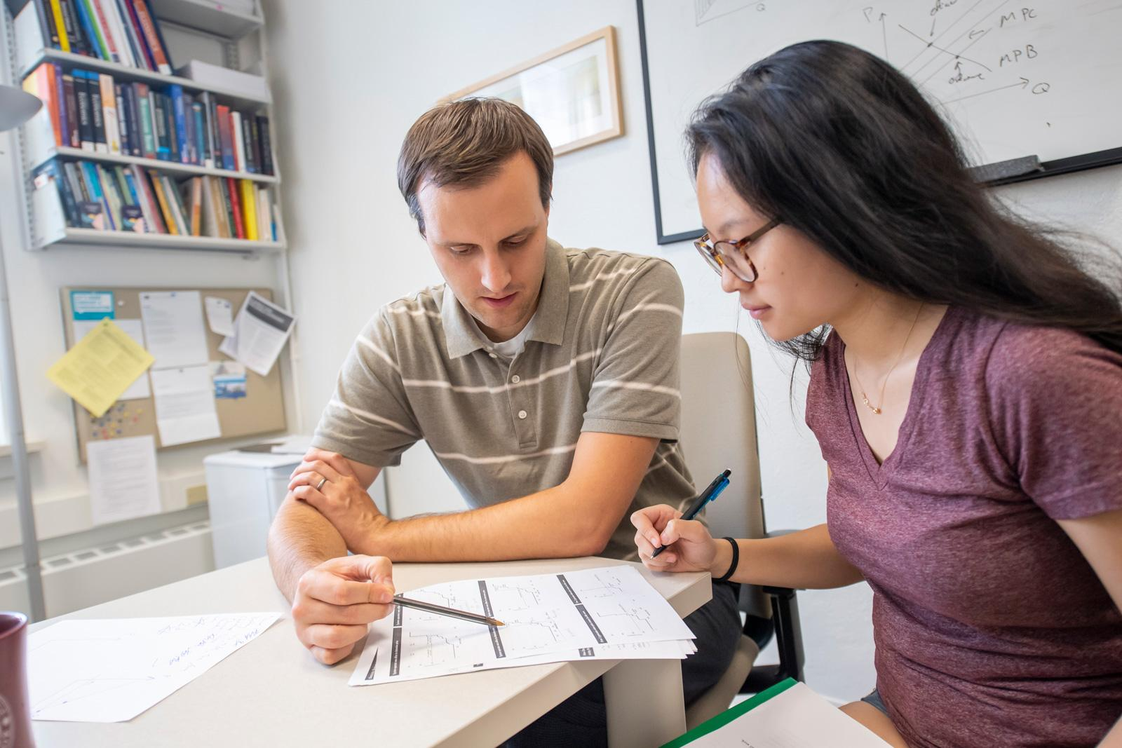 A professor and student review a document in the professor's office.
