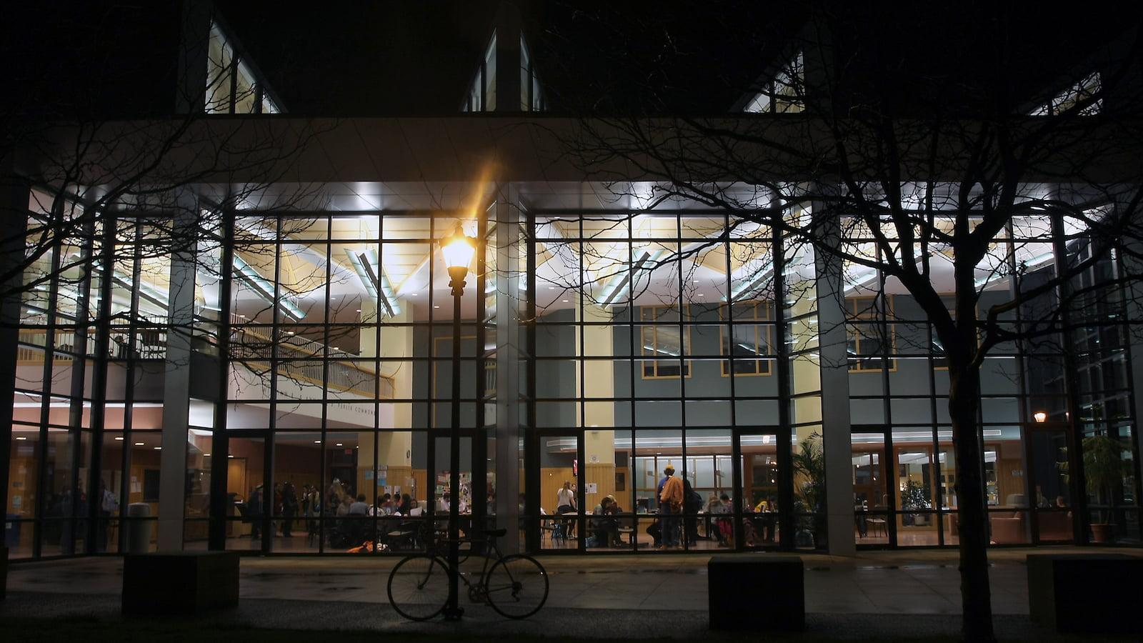 Students studying in the Science Center atrium at night.