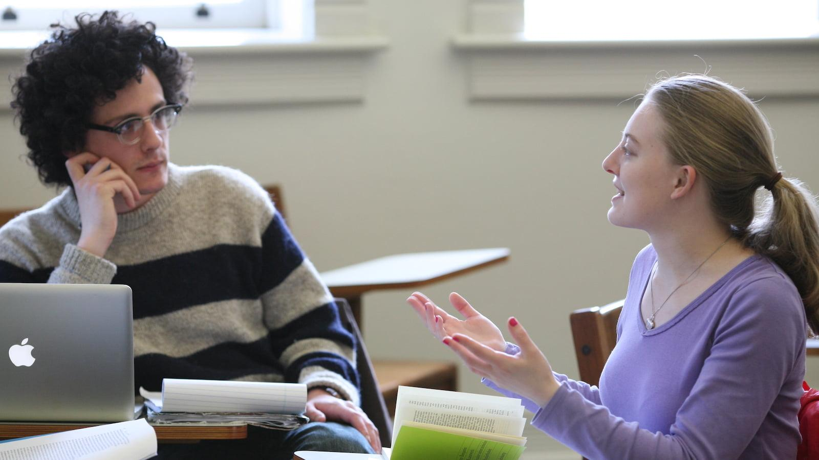 Two students having a conversation in a classroom in Peters Hall.