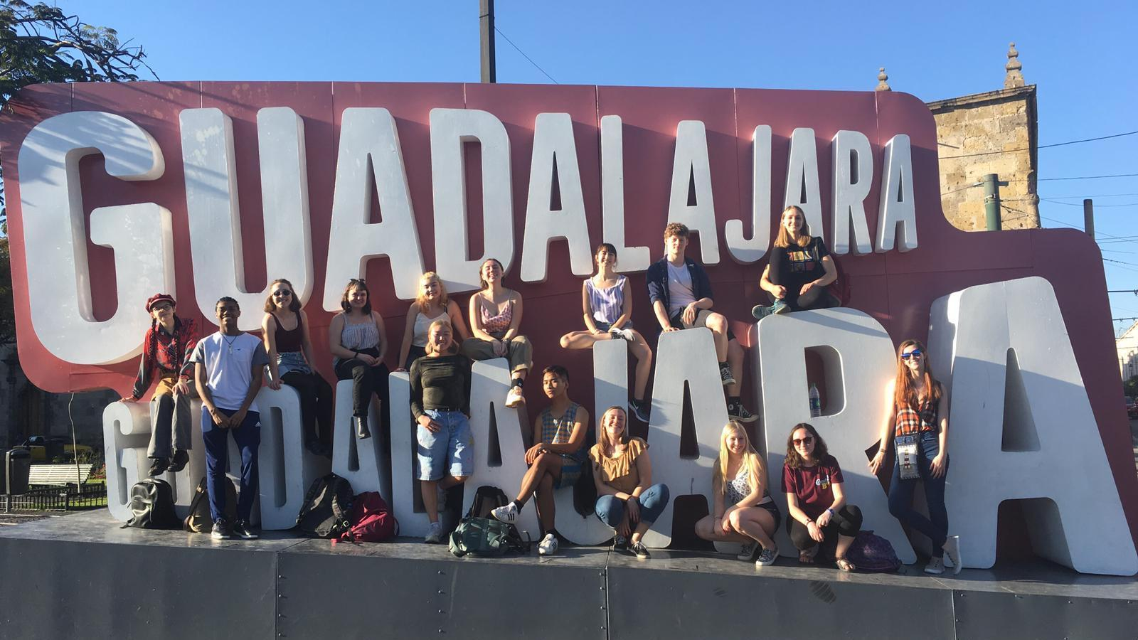 A group of students in front of a large Guadalajara sign.