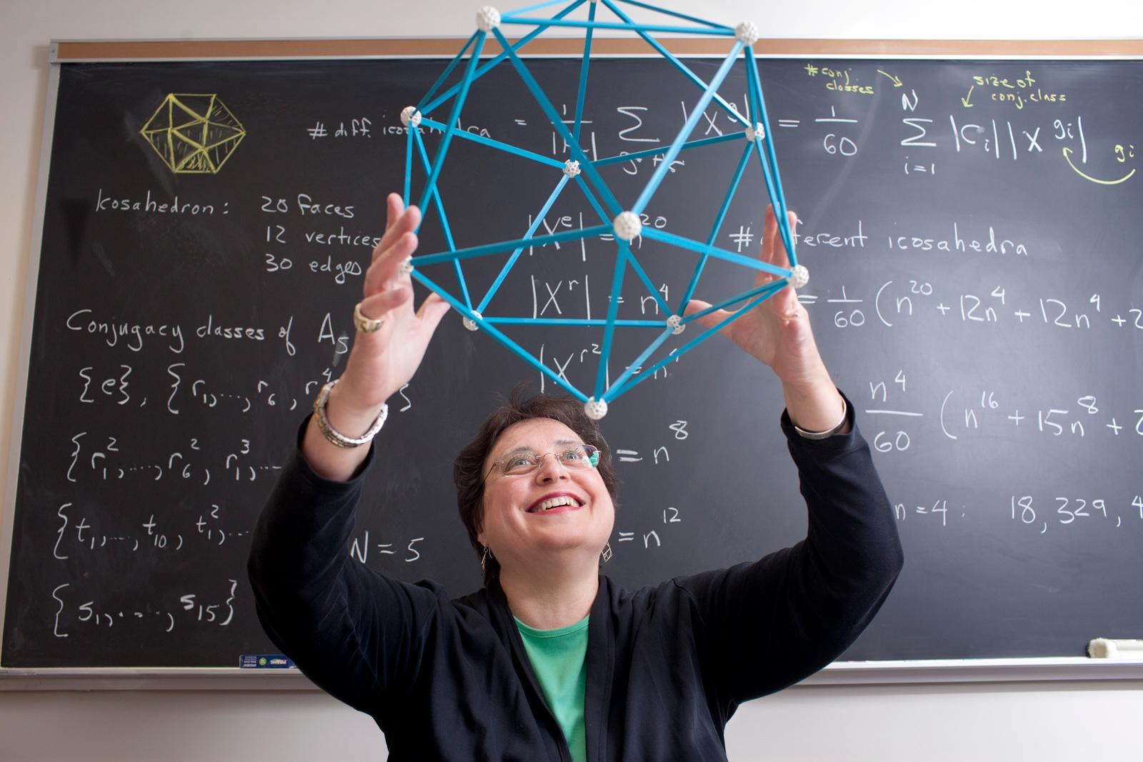 A professor holds a geometric model above her head. The blackboard behind her is covered in equations.