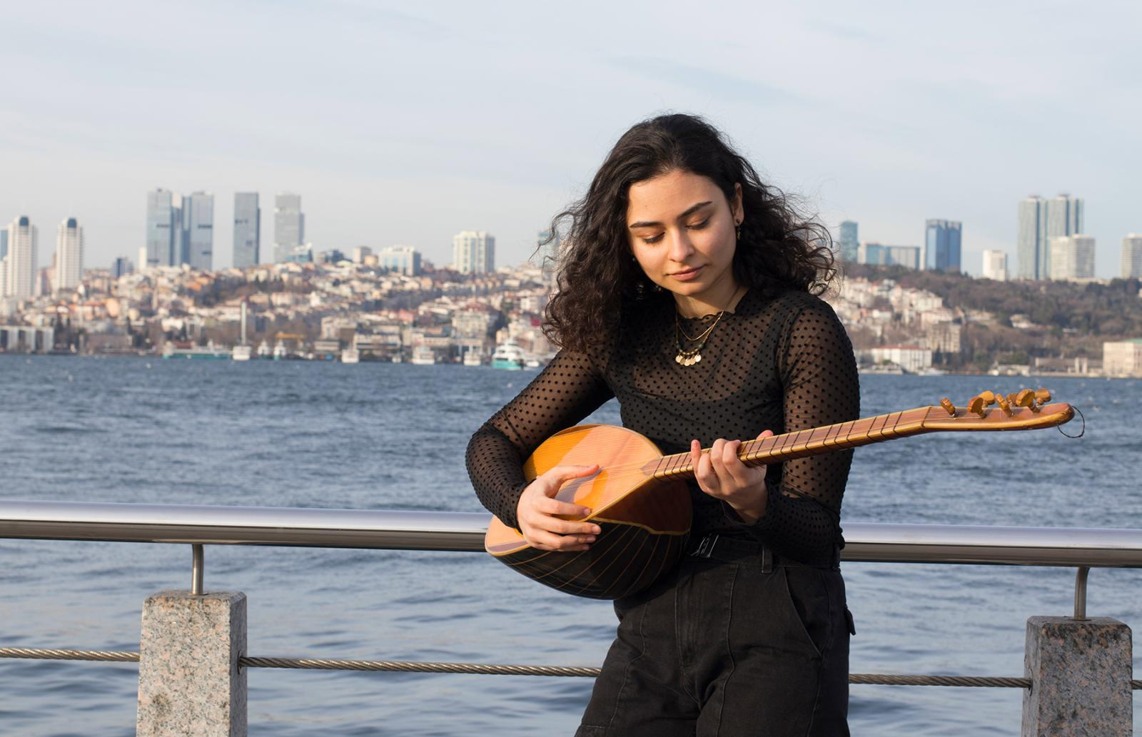 A woman plays a stringed instrument, with water and a city skyline behind her.