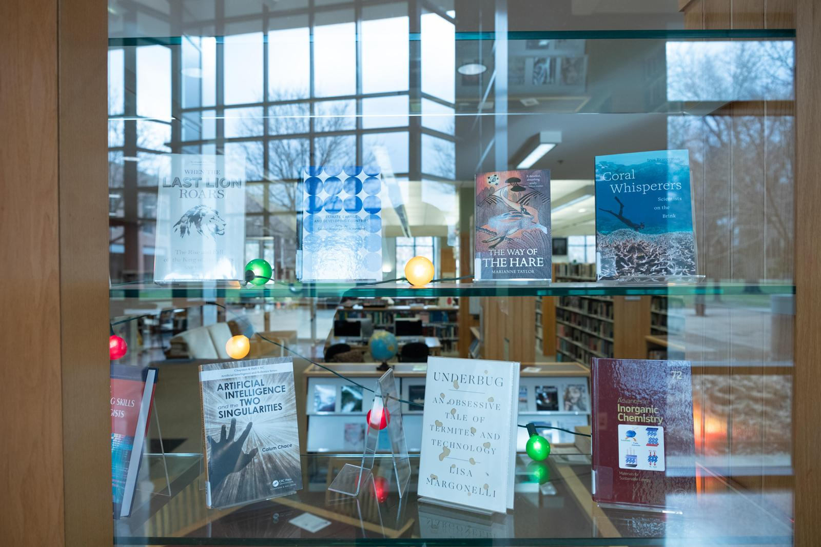 Books are displayed in a glass case in a modern library.
