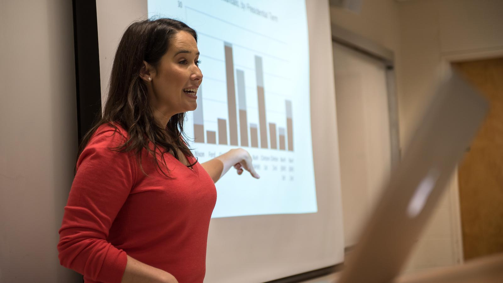 Professor Jenny Garcia pointing at a bar graph on the screen.