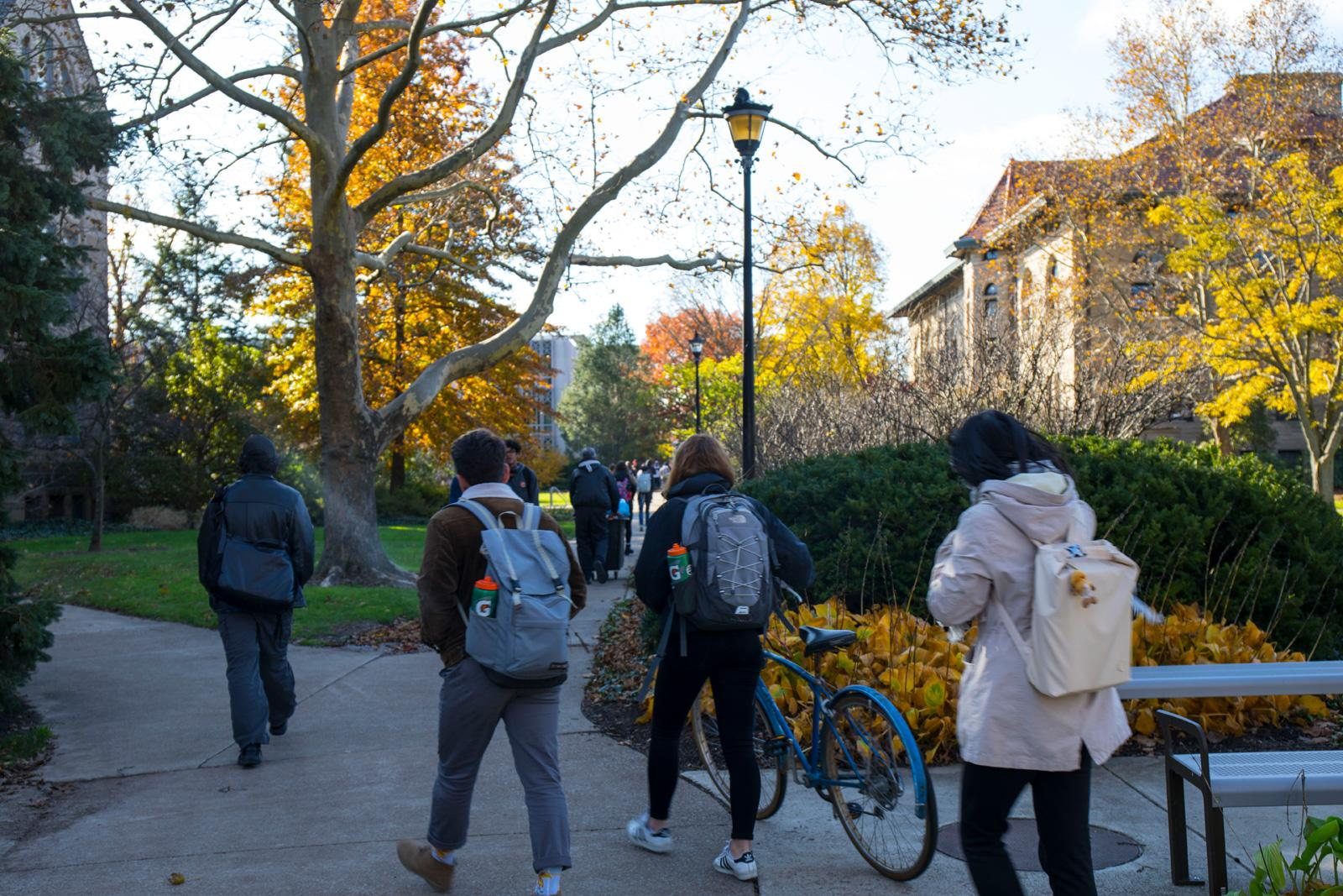 Students with backpacks walk across campus.