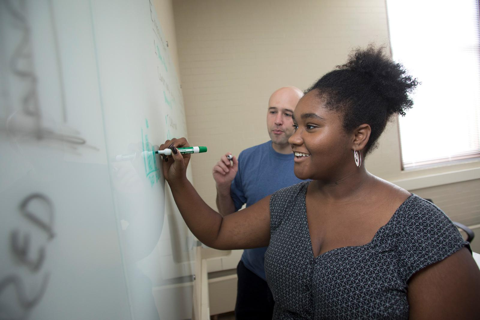 A student writes on a whiteboard while the professor looks on.