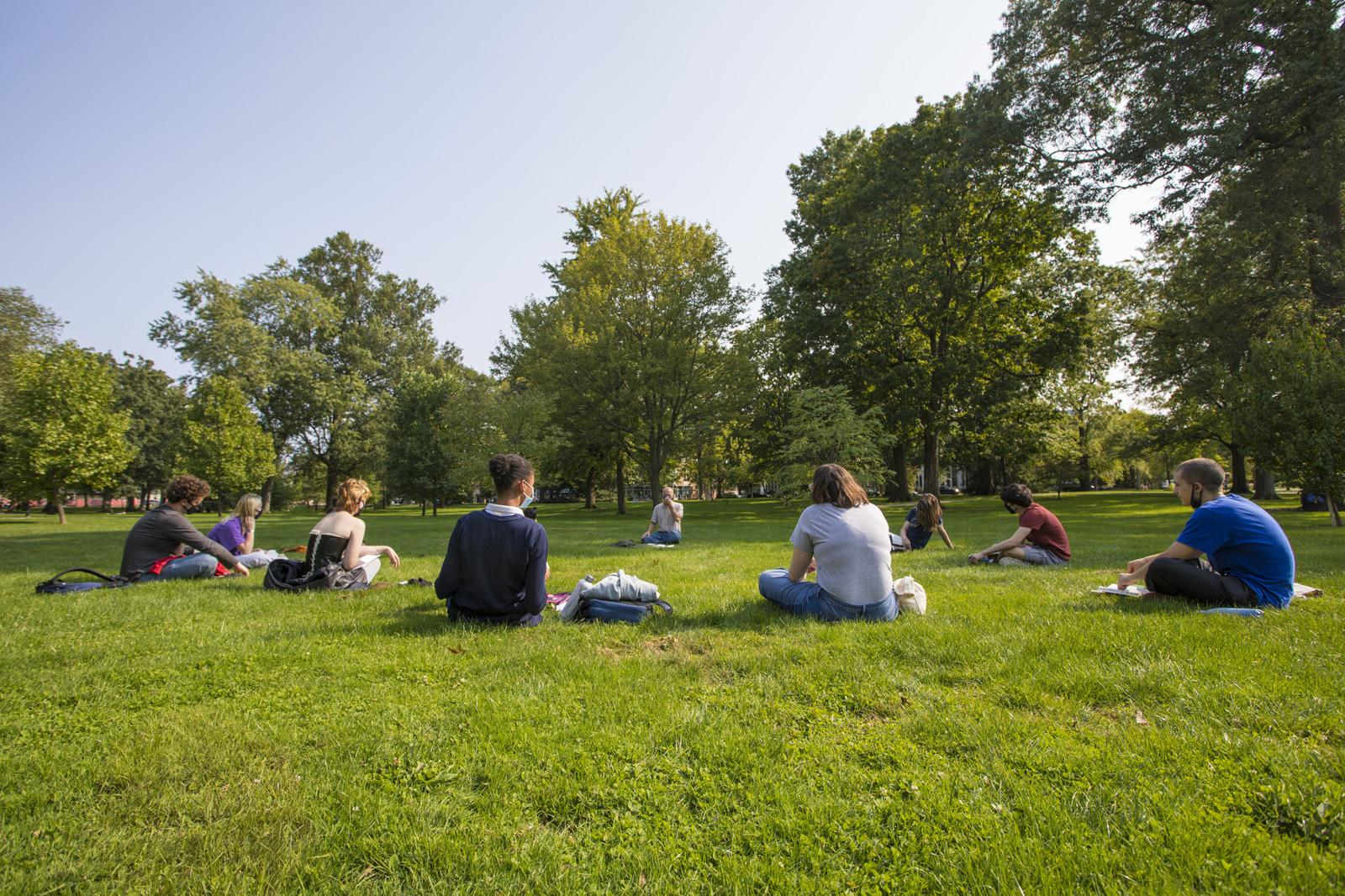 Students sitting in a circle in the grass, spaced widely apart from one another.