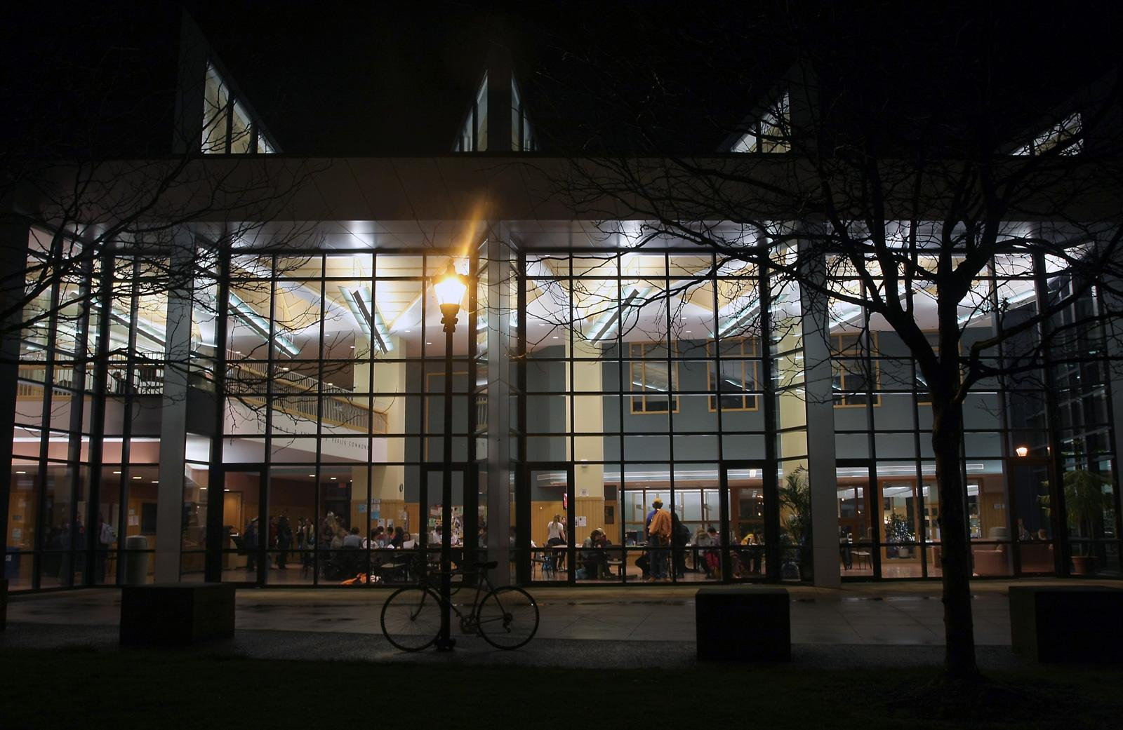 A nighttime view looking into the busy, lit up atrium of the science center.