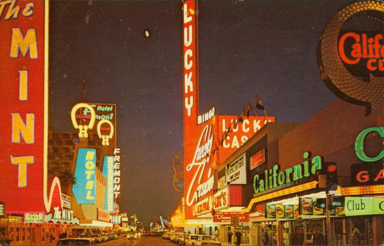 A 1950s city street with many lit up signs including Lucky Casino, The Mint, and hotels.