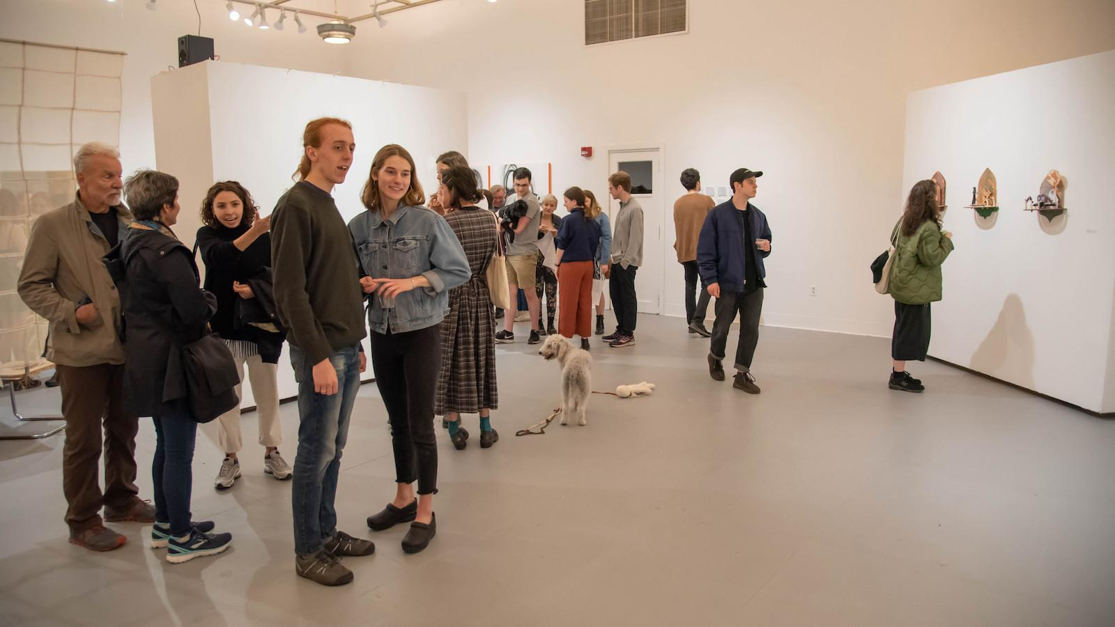 People gathered in a gallery for an art show.