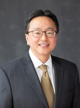 Asian man dressed gray suit with tan tie smiling and wearing glasses.
