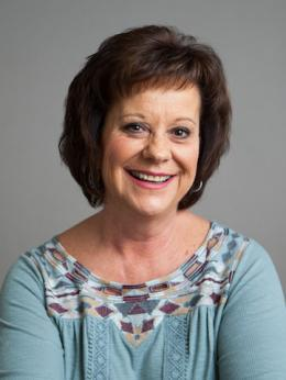 Photo of Dianne Beko short auburn hair wears light teal sweater with brown checked trim around neckline.
