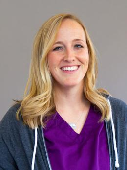 Blond haired Erin Gornall wears hoodie with dark purple scrubs