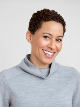 fair skinned smiling black woman in gray turtle neck sweater.