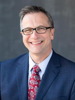 man in navy suit red speckled tie and glasses named Michael Grzesiak.
