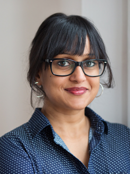 Swapna Pathak in glasses and navy polka dot blouse.