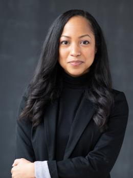 portrait of black woman with shoulder length hair in black turtleneck sweater and blazer.