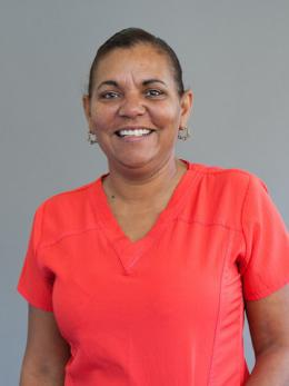 Vicky Gaines wears hair pulled back and has on dark orange scrubs.