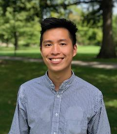 Male Asian student with blue checked shirt standing in park area.