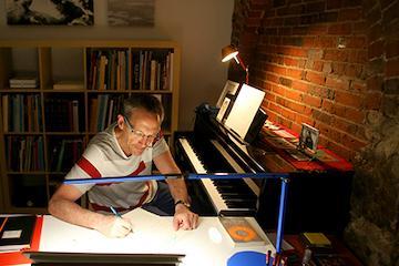 man sittng at deak near piano writing music,