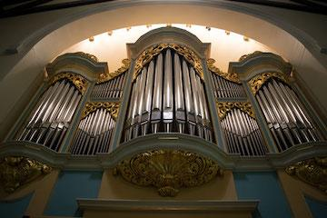three large pipes on an organ.