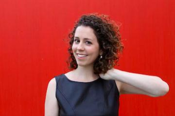 womam with hand in hair in front of red background.