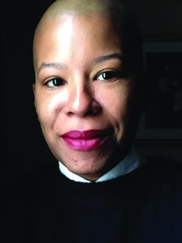 full face of a black woman wearing white collar turned up and black jacket.