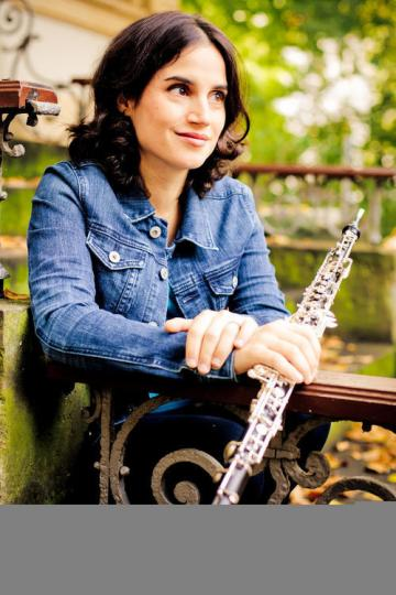 Katherine Needleman holding oboe while sitting outside.