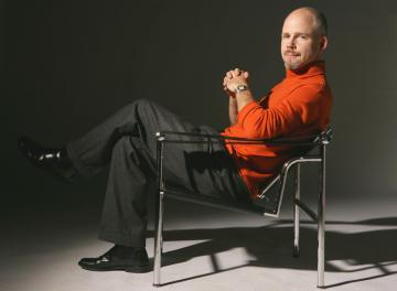 Stephen Burns in an orange shirt and seated in a chair