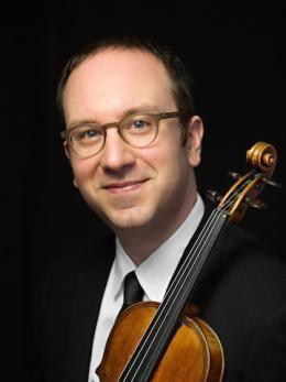 David Bowlin is holding his violin and smiling