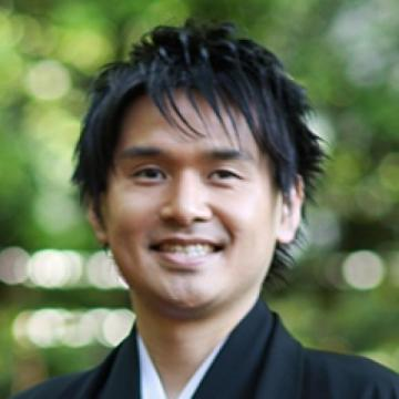 face of a smiling Asian man wearing black jacket and light colored shirt.