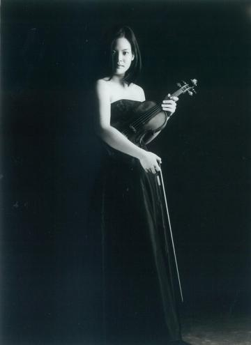 Caroline Chin in long black gown holding her violin