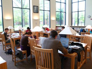 students studying reading at desks in science library