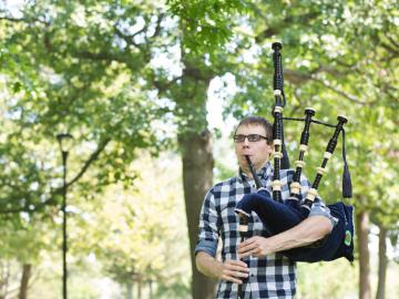 Man in plaid shirt playing bagpipe in a leafy setting