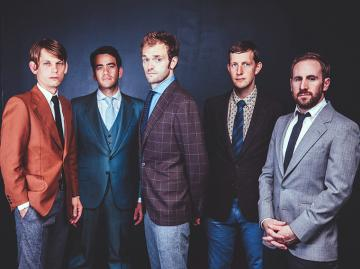 Five men in colorful suits