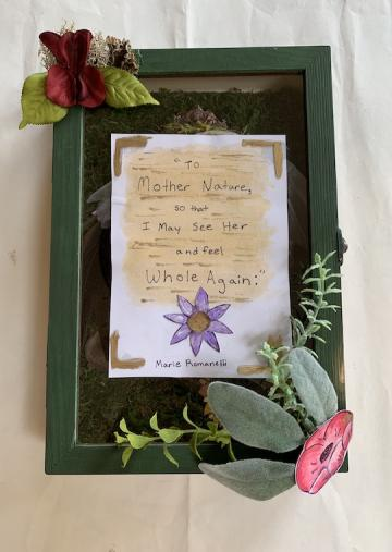 A wooden box framed in glass and flowers.