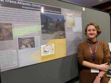 Lucy Haskell standing next to a poster.