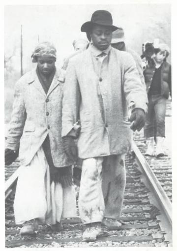 A boy and girl walk next to railroad tracks.